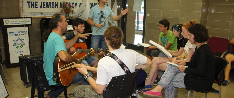 Unge immigranter fra mange verdenshjørner øver på israelske sanger. Målet er å lære 70 mens de er her, smiler direktør Ziona Eisenstein.