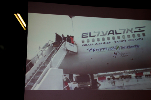 På en storskjerm i ankomsthallen kunne slekt og venner følge med på hvem som kom ned flytrappen. Foto: Mona Ø. Beck