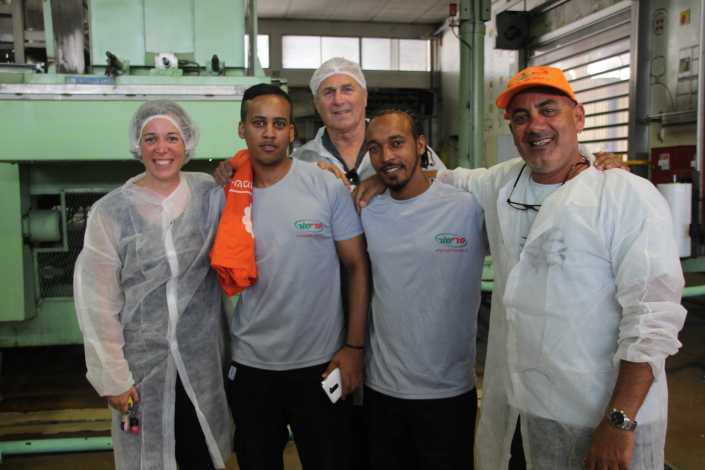 Klart for nytt skift ved Gan Shmuels fabrikk for råvarer til leskedrikker (og blant annet pizza-tomatfyll i Norge). Fra v. Moran Rosenberg, to av de etiopiske ungdommene og fabrikksjef Nir Bendak. Bak titter Itzik Shafran frem. Foto: Mona Ø. Beck