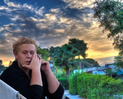 Kvinne i Sør-Israel sitter på trappa. Bak henne ser vi et vakkert landskap. Akkurat nå er det stille mellom rakettene.